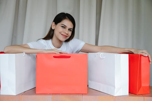 Delighted young woman showing purchases in paper bags and smiling