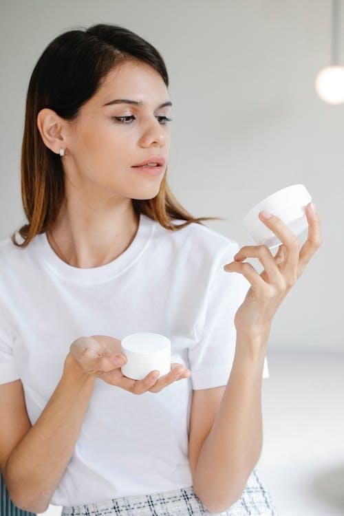 Trendy young lady applying facial cream in studio