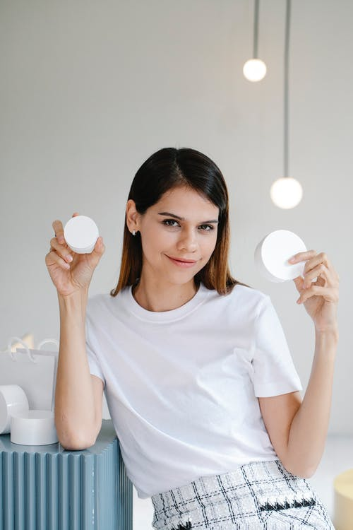 Self assured young female with long dark hair in white t shirt smiling while holding blank jars of cosmetic products in light room