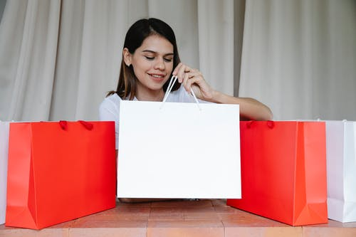 Happy young woman putting shopping bags on table after delivering purchases