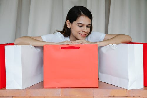 Excited young female leaning on shopping bags and smiling happily