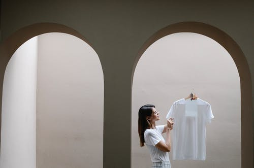 Side view of confident young lady with long dark hair in stylish outfit holding hanger with white t shire while standing near arch in minimalist house