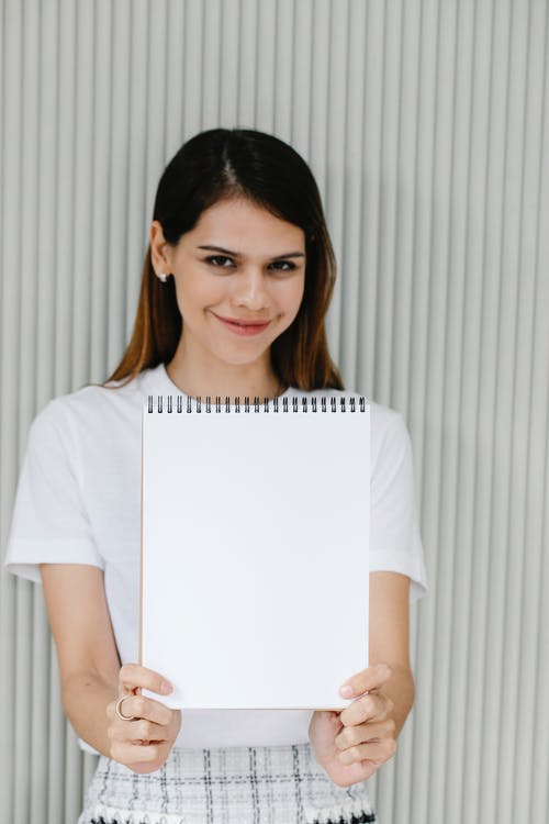 Content female student showing white paper of notepad and smiling at camera