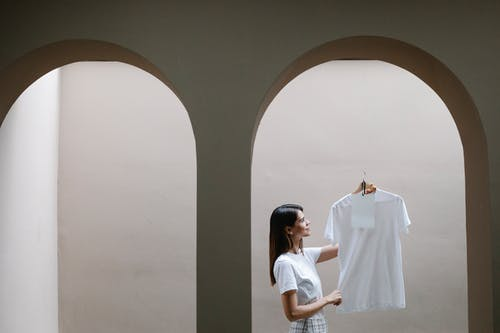 Stylish woman demonstrating t shirt on hanger near arched doorway