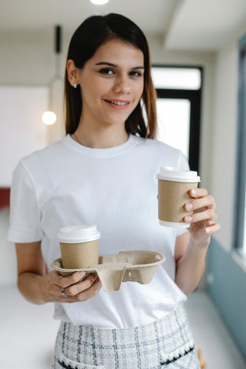 Happy woman smiling and looking at camera while carrying eco friendly cups during coffee break in office