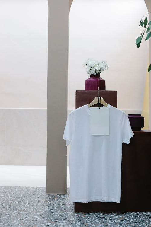 White t shirt with blank label hanging on counter in modern clothes shop
