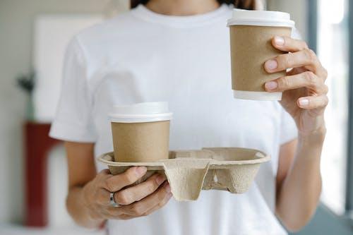 Crop female enjoying takeaway coffee