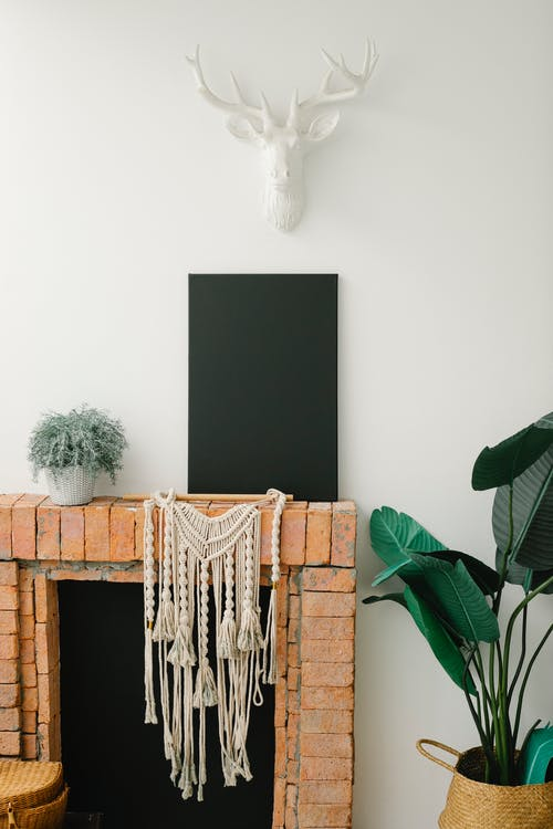 Rectangular black blank canvas placed on brick fireplace against white wall in light moden apaprtment