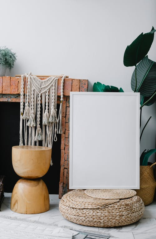 Composition of empty white photo frame placed near brick fireplace and cozy decorations in light room