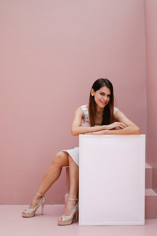Full body cheerful young female sitting near white blank canvas against pink wall and looking at camera with smile