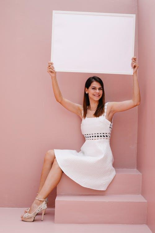 Cheerful woman raising blank canvas against pink wall