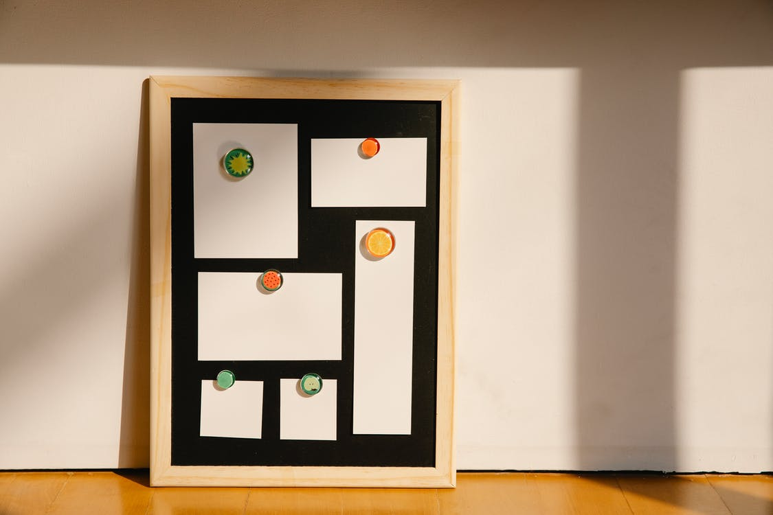 Framed board with blank stickers placed on floor