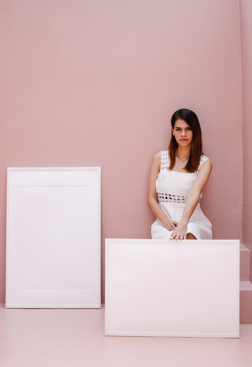 Stylish young female sitting on staircase near blank frames against pink background and looking at camera