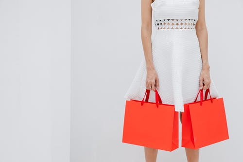 Crop unrecognizable woman carrying red shopping bags in studio