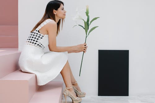 Side view trendy young female with tender flower sitting on staircase near black blank canvas in light room