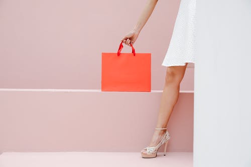 Crop anonymous stylish female in white dress and high heels carrying red shopping bag against pink wall