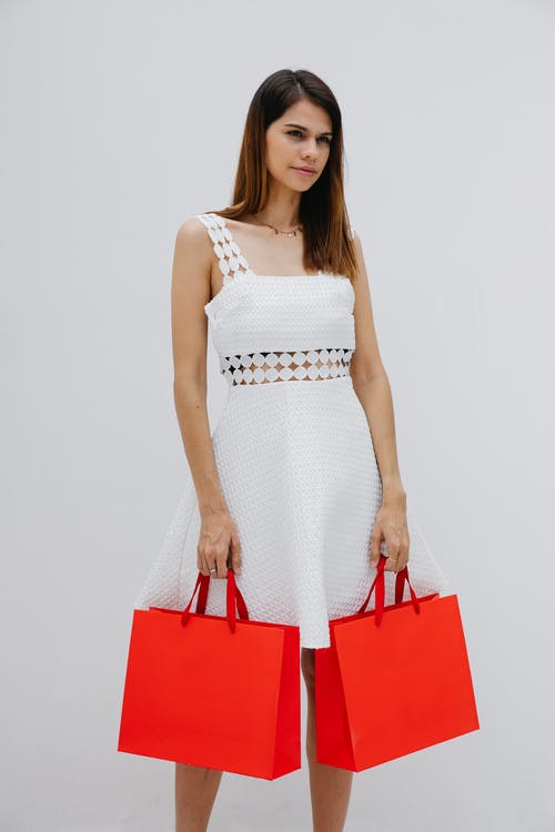 Stylish woman with red paper bags