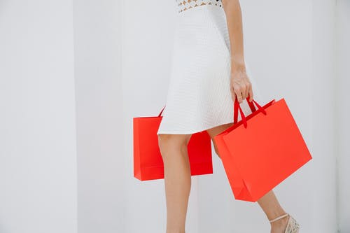 Woman carrying bright red shopping bags