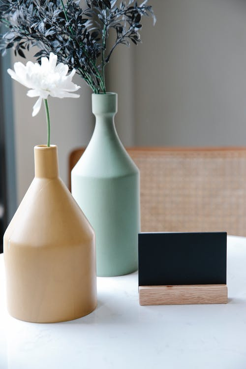 Clay vases with flowers near smartphone holder