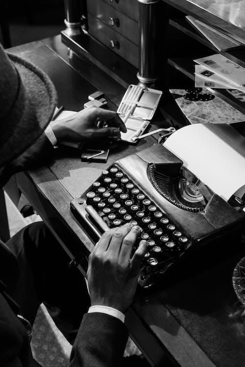 Monochrome Photo of Person Using Vintage Typewriter
