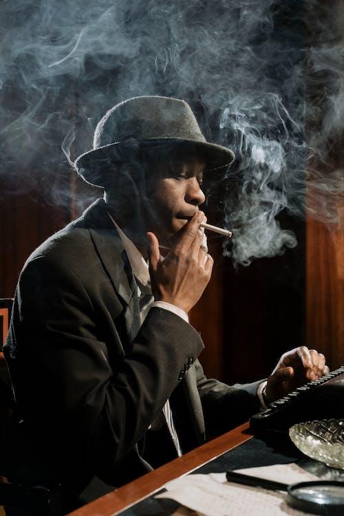 Photo of Man Smoking while Working