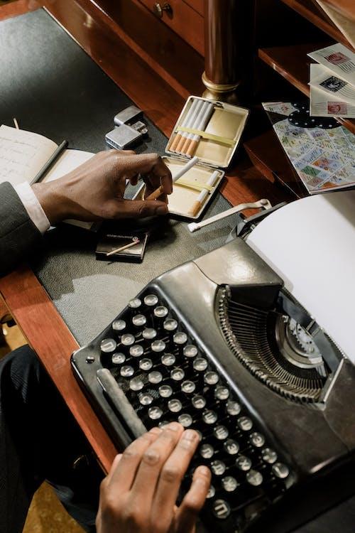 Person Holding White Printer Paper on Black Typewriter
