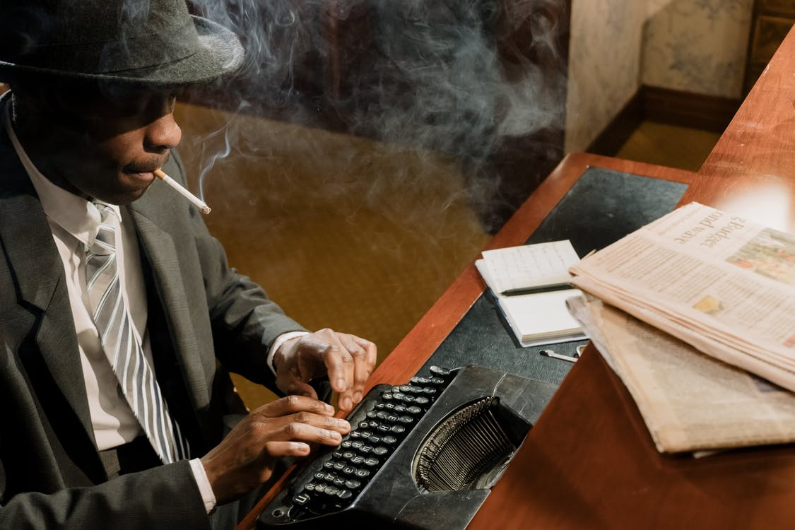 Photo of Detective Typing on a Vintage Typewriter