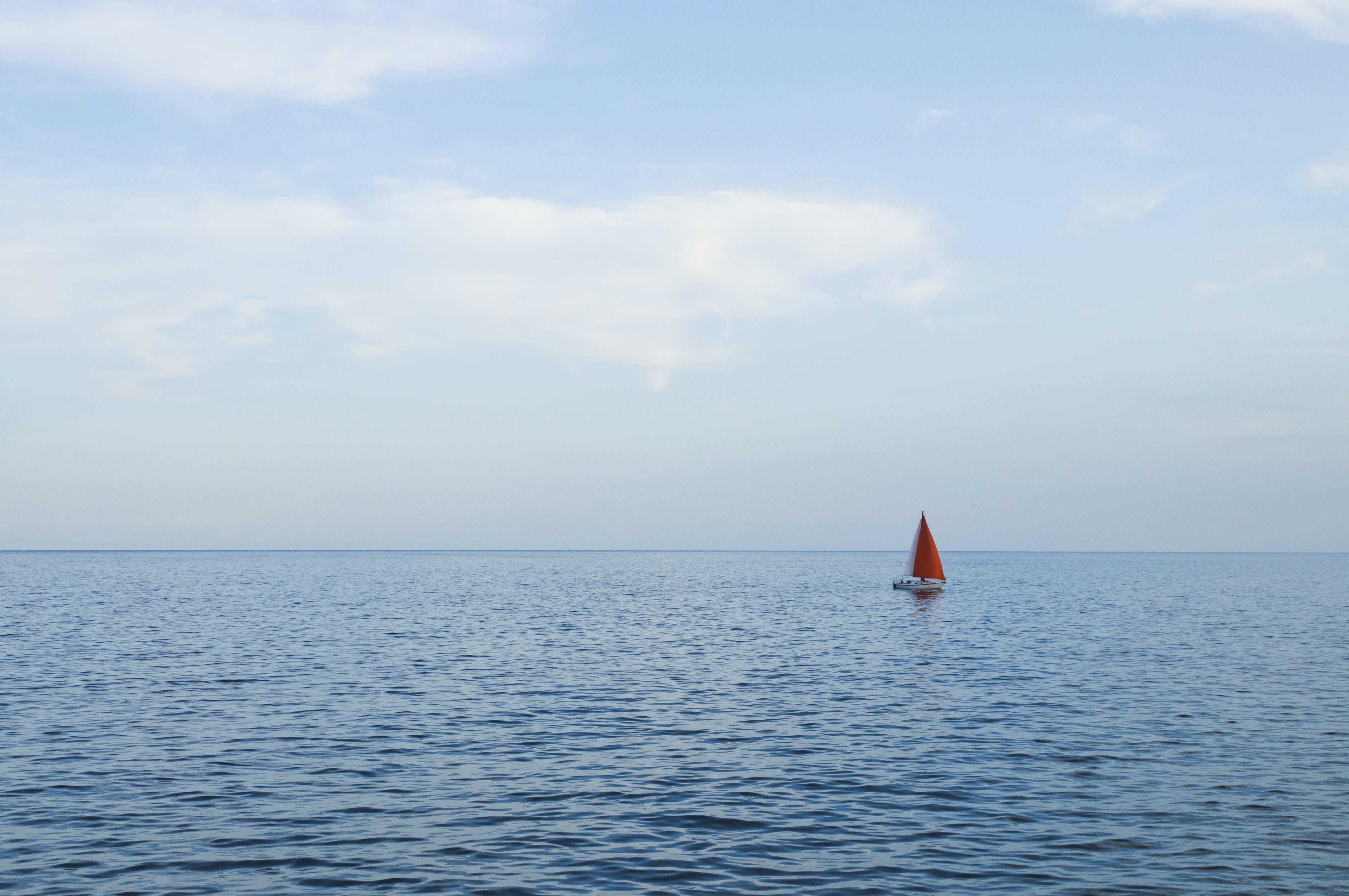 Orange Sailboat on Body of Water