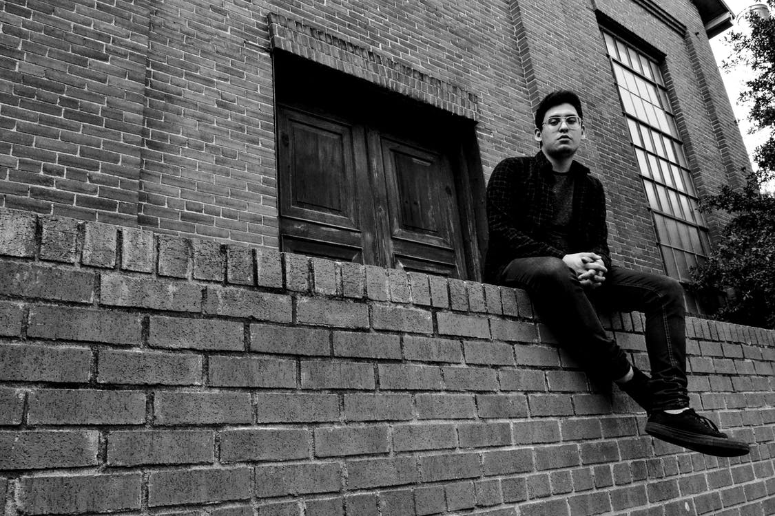 Grayscale Photography of Man Sitting on Brick Fence