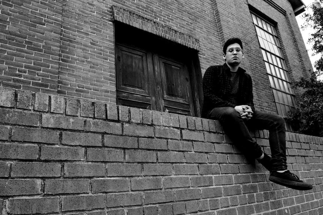 Fotografia Em Tons De Cinza De Um Homem Sentado Em Uma Cerca De Tijolos