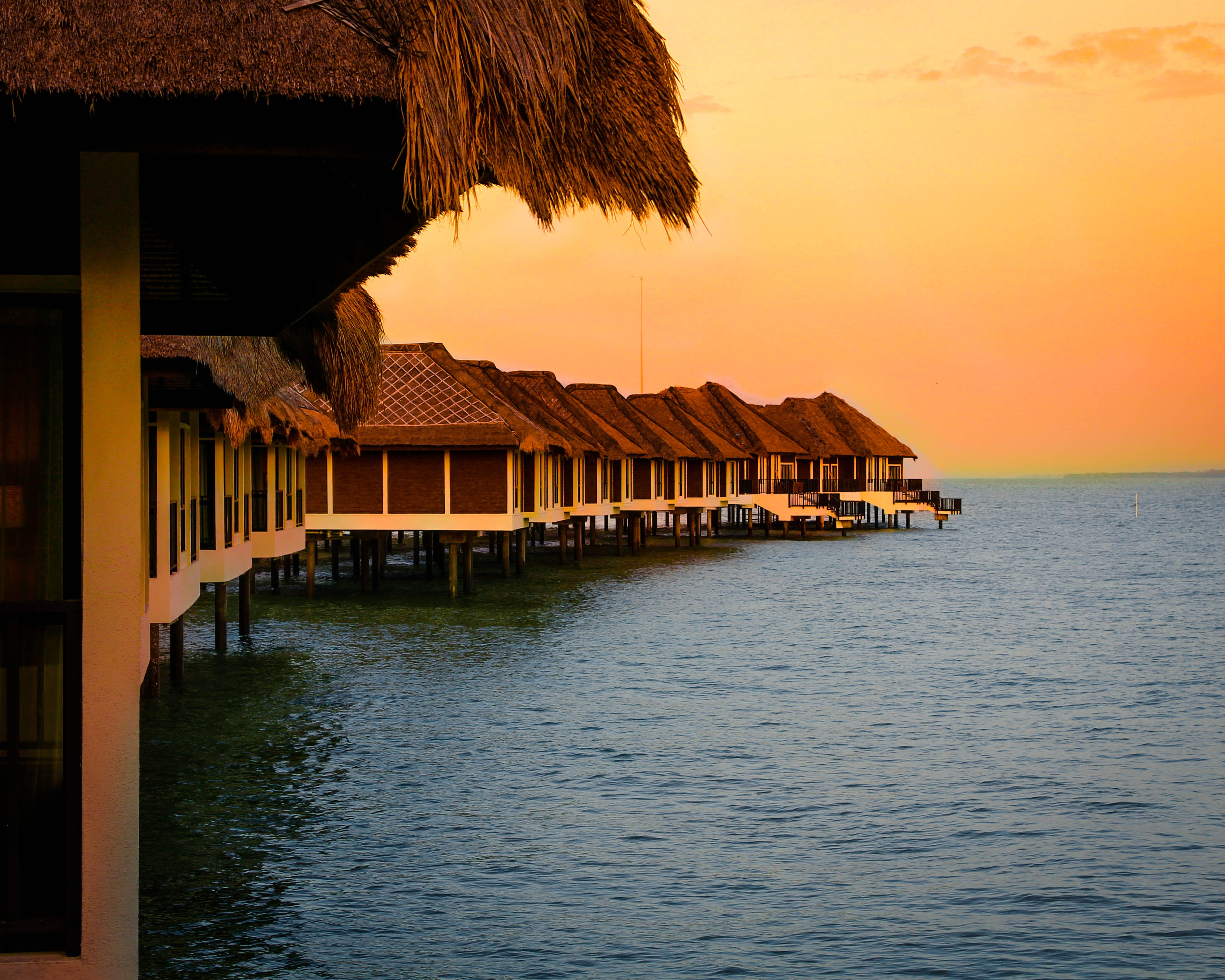 Architectural Photography of Brown Stilt Houses on Top of Sea Under Orange Sky