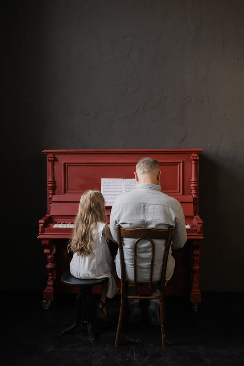 Back View of Grandfather and Granddaughter Playing the Piano