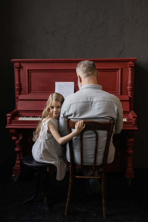 Grandfather and Granddaughter Playing the Piano