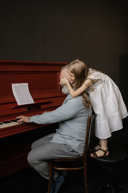 Granddaughter Covering Her Grandfather's Eyes while Playing the Piano