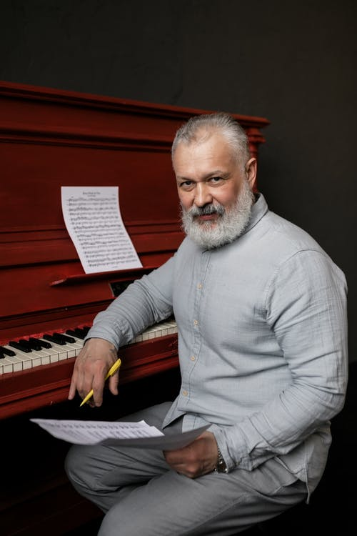 Elderly Man in Gray Long Sleeves Holding a Sheet Music