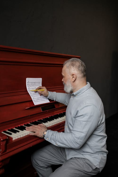 Elderly Man in Gray Long Sleeves Writing in a Sheet Music
