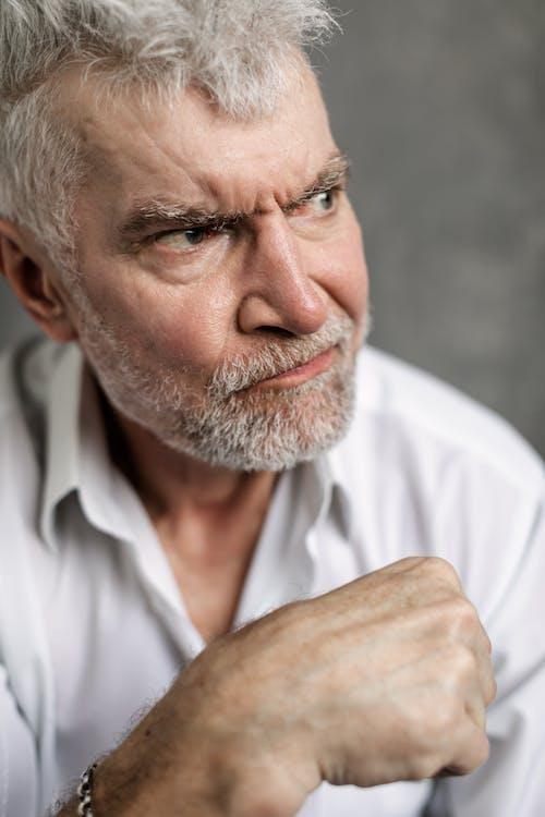 Close-Up Photo of an Elderly Man Looking Grumpy