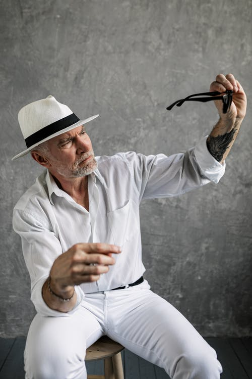 Elderly Man in White Dress Shirt Looking at His Sunglasses