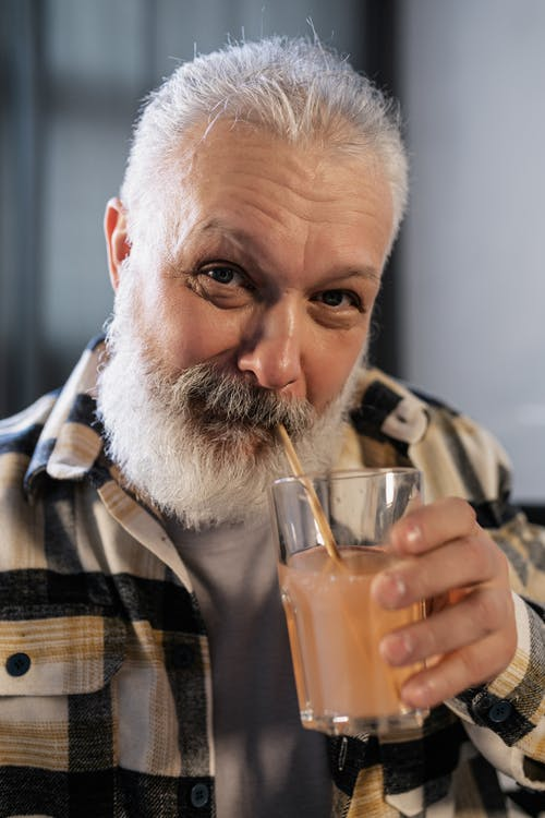 Elderly Man in Plaid Shirt Drinking