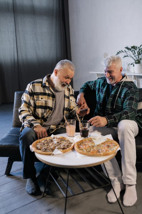 Elderly Men Laughing while Looking at a Smartphone