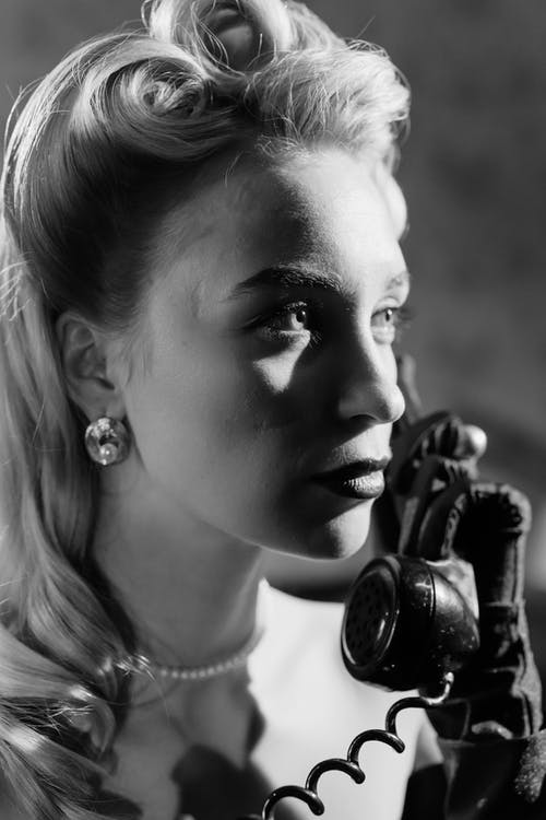 Close-Up Photo of Woman Talking to a Telephone