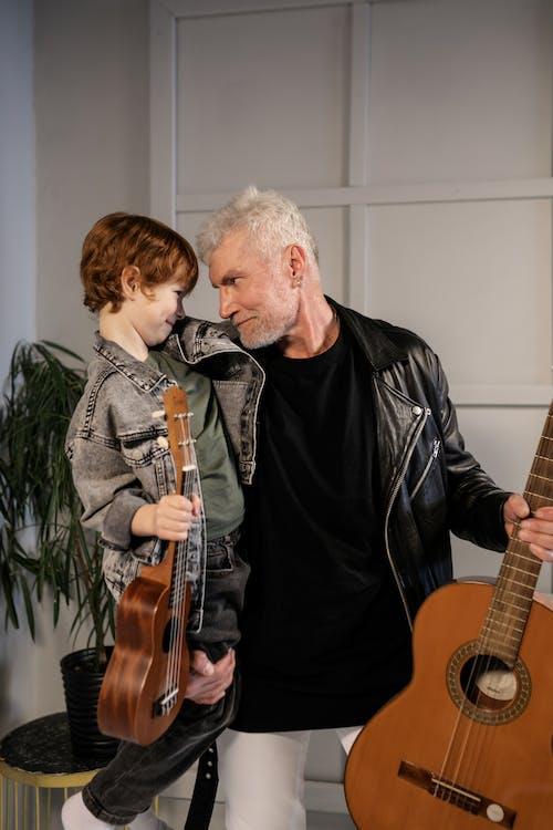 黑色皮夹克的男人在黑色皮夹克的男人旁边弹吉他