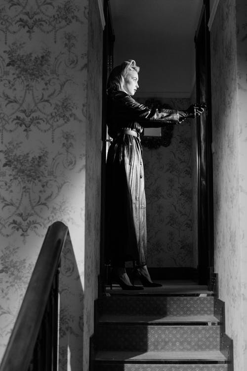 Woman in Black and White Dress Standing on Stairs