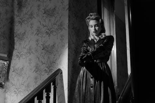 Woman in Black Dress Standing Beside Window