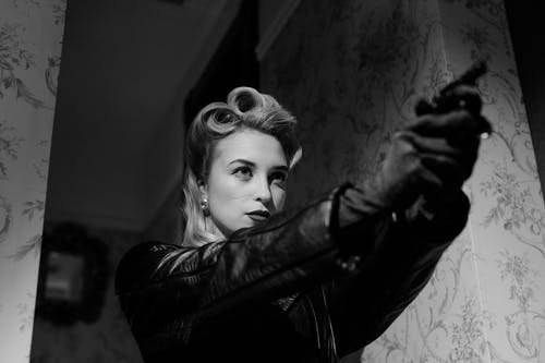 Blonde Woman In Black Leather Coat Pointing A Gun
