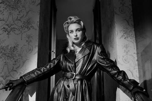 Woman in Black Leather Coat Standing Near Window
