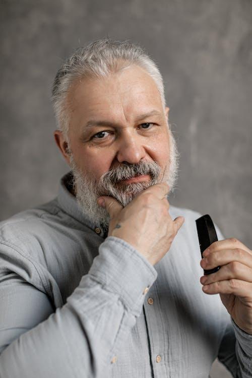 Elderly Man in Gray Dress Shirt Touching His Beard