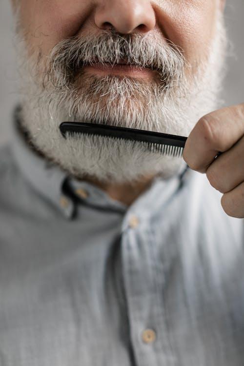 Close-Up Photo of Elderly Man Combing His Beard