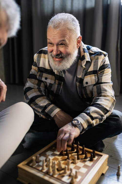 Elderly Man Smiling while Playing Chess