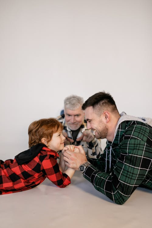 A Family Having Fun Playing Arm Wrestling